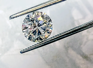 A 2 carat diamond being held up by tweezers