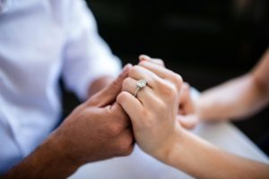 Groom and bride holding hands with ring showing on her finger