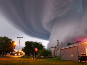 Large tornado moving towards a house in a rural area
