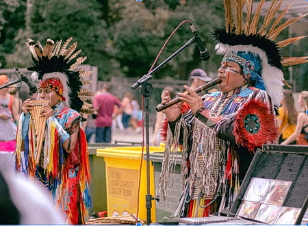 Two Native Americans playing a traditional musical instrument