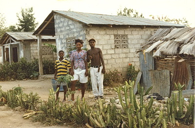 Haitian family outside of their cinder block house